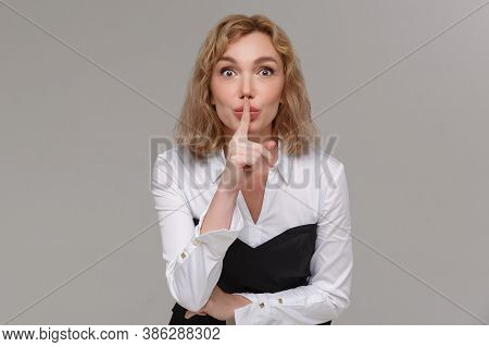Keep My Secret. Serious Young Woman Looking At Camera And Holding Finger On Lips While Standing Agai