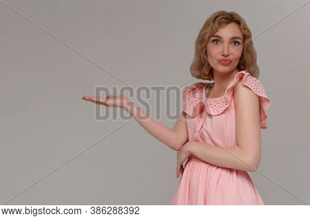Confused Young Beautiful Woman In Pink Dress, Holding Imaginary Object On The Palm. Isolated On Gray