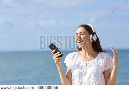 Happy Teen Sings Wearing Wireless Headphones And Smart Phone On The Beach