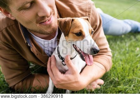Partial View Of Young Man Cuddling Jack Russell Terrier Dog While Relaxing On Green Grass