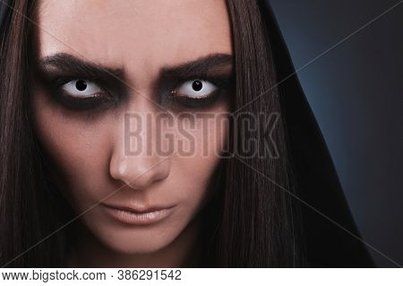 Mysterious Witch With Spooky Eyes On Color Background, Closeup