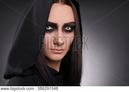 Mysterious Witch With Spooky Eyes On Dark Background, Closeup
