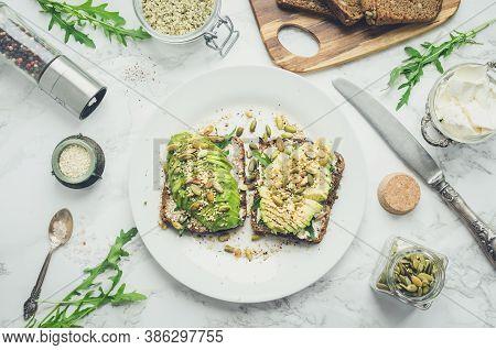 Healthy Avocado Toasts For Breakfast Or Lunch With Rye Bread, Cream Cheese, Arugula, Sliced Avocado,