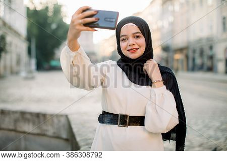 Portrait Of A Young Arabian Woman In Black Hijab Using Mobile Phone On The Street, Making Selfie Pho