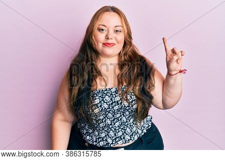 Plus size caucasian young woman wearing casual clothes smiling with an idea or question pointing finger up with happy face, number one