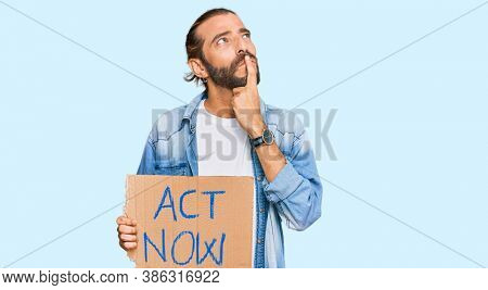 Attractive man with long hair and beard holding act now banner serious face thinking about question with hand on chin, thoughtful about confusing idea