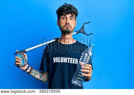 Young hispanic man holding plastic bottle and litter picker to recycle puffing cheeks with funny face. mouth inflated with air, catching air.