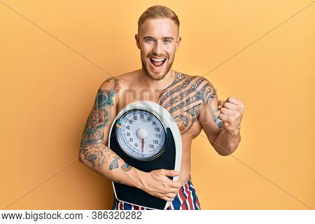 Young caucasian man holding weight machine to balance weight loss screaming proud, celebrating victory and success very excited with raised arms