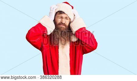 Handsome young red head man with long beard wearing santa claus costume suffering from headache desperate and stressed because pain and migraine. hands on head.