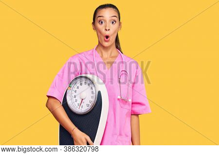 Young hispanic woman as nutritionist doctor holding weighing machine scared and amazed with open mouth for surprise, disbelief face