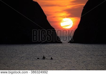 Three Silhouetted Unidentifiable Surfers Return From The Sea In Front Of Gull Rocks At Holywell Bay