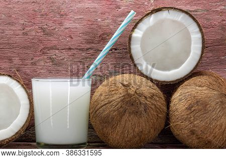 Glass Of Fresh Coconut Milk And Halved Fruits On Aged Wooden Background