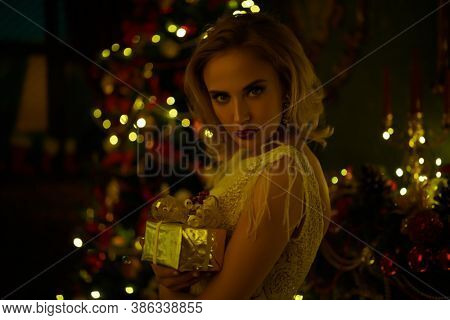 Christmas and New Year concept. Fashionable young woman wearing luxurious evening dress and with beautiful evening makeup and hairstyle in the fairy beautiful Christmas interior. Jewellery.