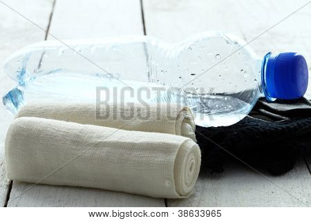 Bottle of fresh water, gloves, and bandages over wooden table