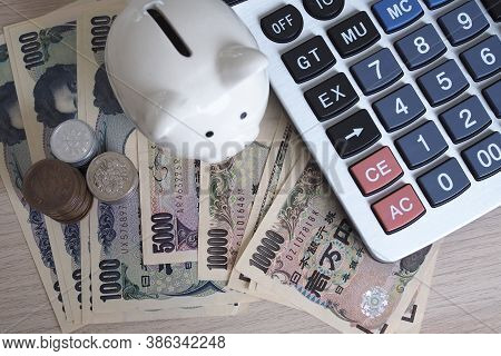 Piggy Bank And Calculator Placed With Japanese Yen Banknotes And Japanese Yen Coins For Money Concep