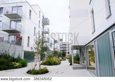 Sidewalk In A Cozy Courtyard Of Modern Apartment Buildings Condo With White Walls.