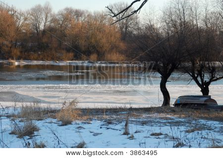 trees and boat on the bank of frozen river at cold sunny blue winter evening poster