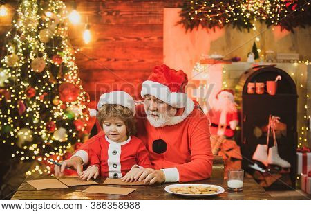 Christmas Helper And Santa Writing Or Reading Letter Home Near The Christmas Tree. Portrait Of Cheer