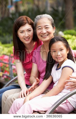 Female Multi Genenration Chinese Family Group Sitting On Bench In Park Together