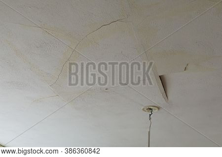 A Plastered House Ceiling Broken By A Water Leak. Rain Or Tap Water Caused Serious Damage.