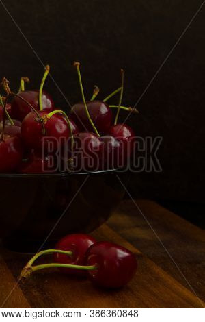 A Moody Photo Of A Bowl With Fresh Cherries.