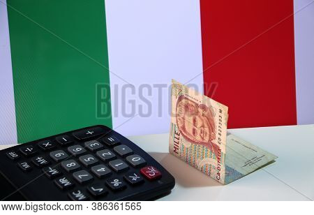 One Thousand Lire Of Italy Banknote With Black Calculator On The White Floor With Italia Flag Backgr