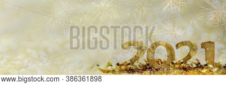 2021 Golden Figures In Glitter And Ribbon On Abstract Blur Light And Firework Background