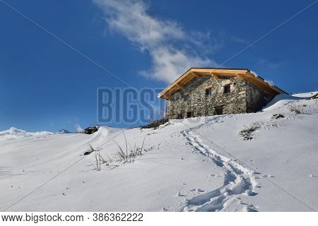 Traditional Alpine Chalet At The Top Of Snowy Mountain Under Blue Sky