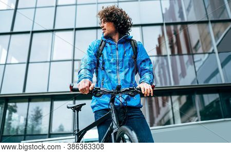 Young Man In Blue Raincoat Standing With His Bike After Cycling In The Street On A Rainy Day. Curly