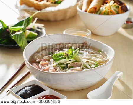 vietnamamese meal with beef pho bo soup accompanied by hoisin sauce and sriracha