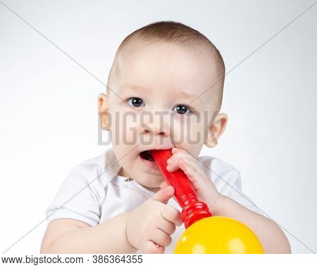 Photo Of A Eleven-month-old Baby With Rattle In Mouth