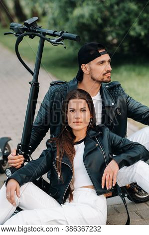 Portrait Of A Couple Sitting Near Electric Scooters, Enjoying Time In Nature Together, Two Lovers On