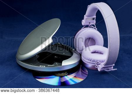 Cd And Cd Player And Headphones Isolated On A Blue Background
