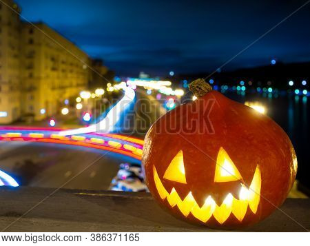 Halloween Pumpkin On The Background Of The Night City. Multi-storey Buildings, A River And Streaks O