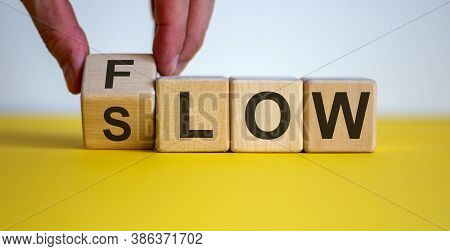Be Slow Or In The Flow. Male Hand Turns A Cube And Changes The Word 'slow' To 'flow'. Beautiful Yell