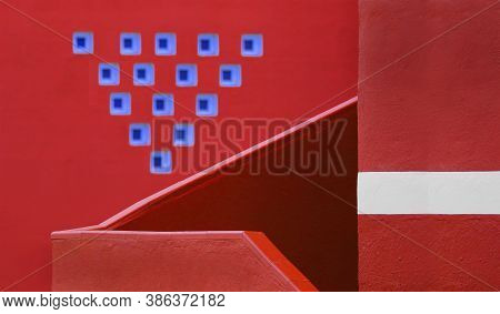 A Ladder And A Red Handrail With A Red Wall And Blue Figures, Polygons And Decorative Red Handrails
