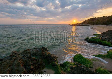Sunrise At The Black Sea. Wonderful Calm Landscape With Rocks On The Beach Beneath A Cloudy Sky. Vel