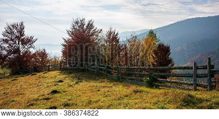 Mountainous Carpatian Rural Landscape In Autumn. Beautiful Scenery With Wooden Fences On Grassy Roll