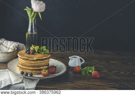 Pancake With Strawberry, Blueberry And Mint In Ceramic Dish, Syrup From Small Ceramic Jar And Flower