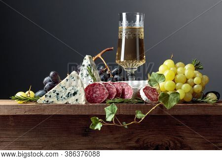 White Wine And Snacks On An Old Wooden Table. Glass Of Wine, Blue Cheese, Dry-cured Sausage, Grapes,