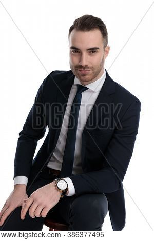 Charming businessman leaning on his leg while sitting on a stool on white studio background