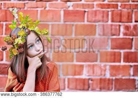 A Girl In An Autumn Wreath Conceivedly Holds Her Hand To Her Face. Brick Wall Background.