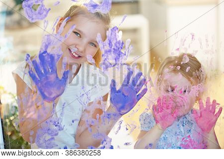 Two girls paint many handprints on a pane with finger paint