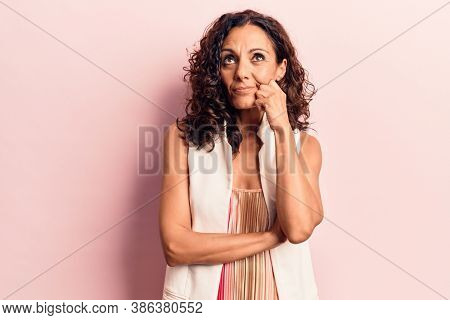 Middle age beautiful woman wearing casual vest thinking concentrated about doubt with finger on chin and looking up wondering
