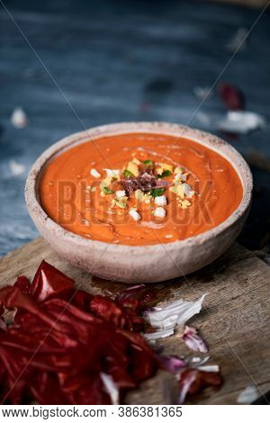 closeup of an earthenware bowl with fresh made spanish salmorejo cordobes or porra antequerana, a cold tomato soup topped with serrano ham, boiled egg and green pepper, on a gray rustic table