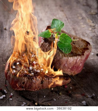 Grilled bbq steaks with fire flames