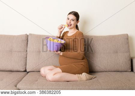 Pregnant Woman Sitting On The Sofa Is Eating Chips Because Of Salt Cravings. Unhealthy Junk Food Dur