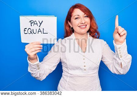 Young redhead woman asking for equality economy holding paper with pay equal message smiling with an idea or question pointing finger with happy face, number one