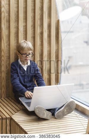 Concentrated Boy In Glasses Gazing At The Computer Screen