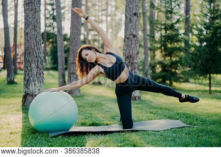 Outdoor Shot Of Active Brunette Woman In Sportswear Poses On Yoga Mat, Does Stretching Exercises Wit
